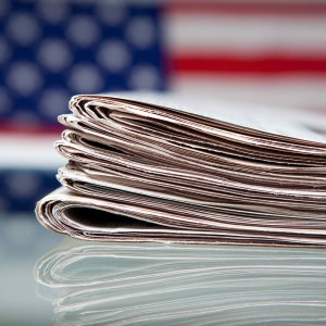Photo - stack of newspapers in front of American flag