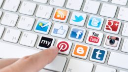 Kiev, Ukraine - May 20, 2013 - Hand pointing on keyboard with social media logotype collection of well-known social network brand's placed on keyboard buttons. Include Facebook, YouTube, Twitter, Google Plus, Instagram and more other logos.