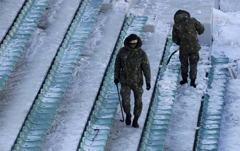 Soldiers clear snow and ice from the seating area at the Alpensia Ski Jumping Center ahead of the 2018 Winter Olympics in Pyeongchang, South Korea, Wednesday, Feb. 7, 2018. (AP Photo/Charlie Riedel)